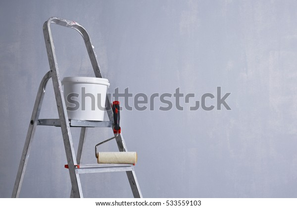 Ladder with paint and roller standing in empty room