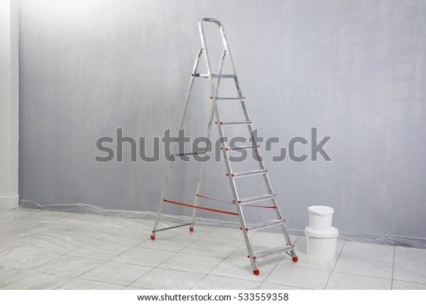 Ladder with paint standing in empty room
