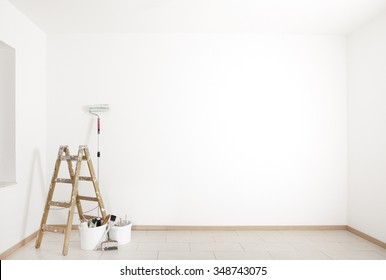 ladder and painting accessories are in an empty room
