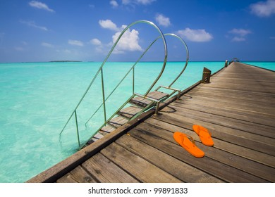 ladder to the sea from a jetty; view to tropical island with beach and palms
