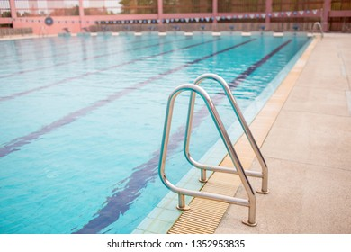 Ladder stainless handrails for descent into swimming pool. Swimming pool with handrail . Ladder of a swimming pool. Horizontal shot.
