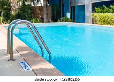Ladder stainless handrails for descent into swimming pool.