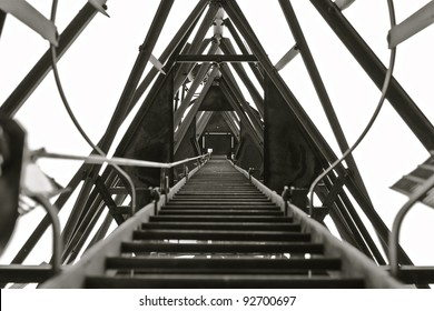 A ladder that leads to the top of a Radio/Communication Mast taken in Black & White.