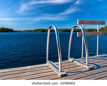 Ladder to water on pier on lake in beautiful nature