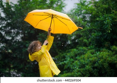 Laddie with a bright yellow umbrella in the rain. He loves a rain and rejoices. Behind the back of the boy a beautiful wet bush.