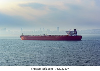Laden crude oil tanker approaches the port of Qingdao along Jiaozhou Bay shore in the morning fog.