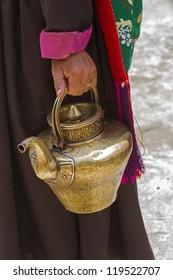 Ladhaki woman carries a tea pot, Ladakh, Indien