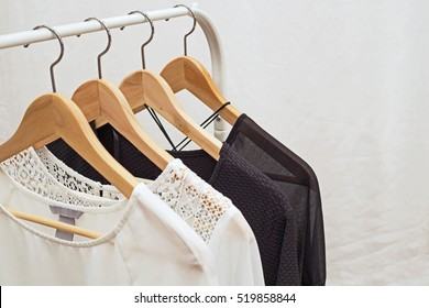 Ladies blouses on wooden hangers. Two white and two black laced  blouse, fashion background
