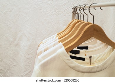 Ladies blouses and shirts on wooden hangers, fashion background