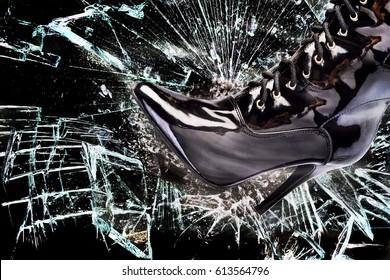 Ladies boot breaking glass window pane.