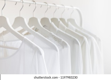 Ladies chiffon blouses hang on white wooden hangers. White lace blouses and jacket.  Fashion background