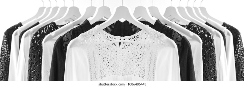 Ladies chiffon blouses on white wooden hangers. White and  black lace blouses.  Monochromate Fashion Banner background. Selective focus