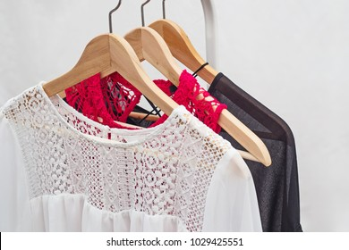 Ladies chiffon blouses on wooden hangers. Two white and two black laced  blouses.  Fashion background