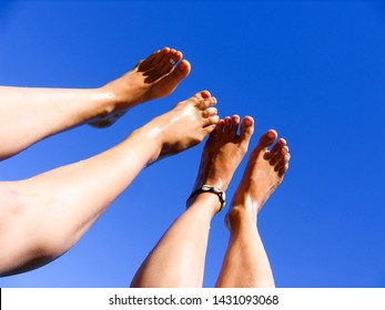 ladies feet legs in air outside with blue sky background