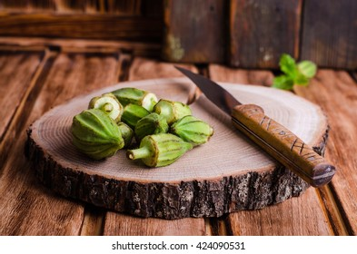 Ladies' finger or okra on round wooden chopping with some slices and knife.  Preparation of these healthy fresh edible green seed pods for cooking.  Selective focus
