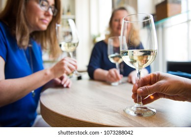 Ladies friends night out wine tasting with white wine together at happy. hour smiling and laughing