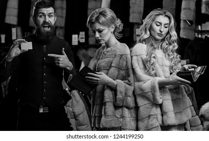 Ladies and gentleman buy overcoats. Guy with beard and women in furry coats. Elegance and glamour concept. Man and girls with busy faces hold wallets pointing at credit card on clothes background