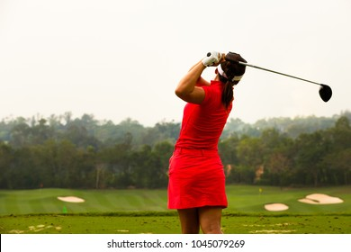 Ladies golfer in red dress finished the golf swing.