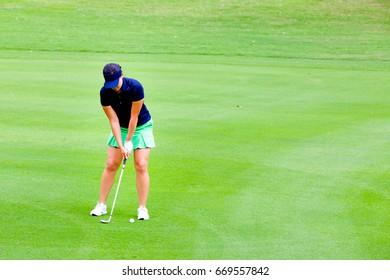 Ladies golfers are swinging golf in the fairways.