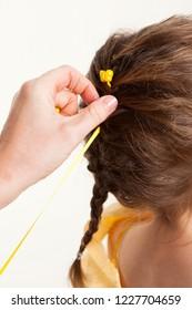 A ladies hand braiding a little girls brown hair