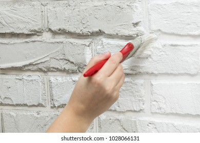ladies hand painted brick brush white wall. Renovation work. White background.