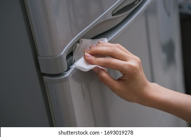 Ladies hand wiping the handle of the fridge door to prevent the spread of bacteria and virus. Personal hygiene concept.