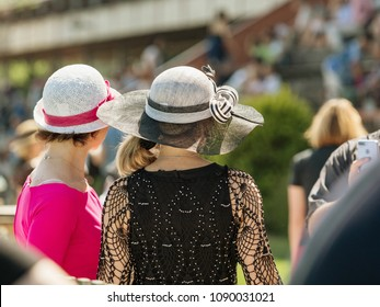 Ladies with hats on the race track. Romantic summer hats. Retro style summer romance in sunny day.