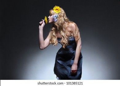 Ladies with long hair in a black dress with flowers in her hair and arm