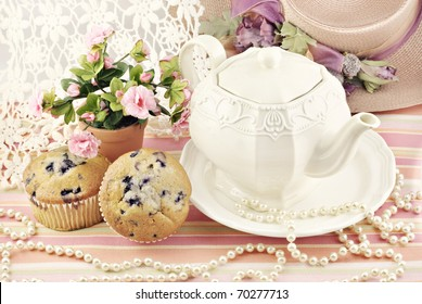 A ladies pretty tea party with blueberry muffins, antique lace and pearls