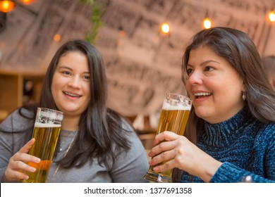 Ladies sharing moments with drinks, one looks at camera smiling