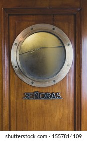 Señoras, Ladies sign on a very old boat door with a porthole window