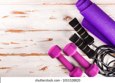 Ladies Sports Accessories such as dumbbells, yoga mat and skipping rope. Fitness, sport and healthy lifestyle concept. Top view, copy space