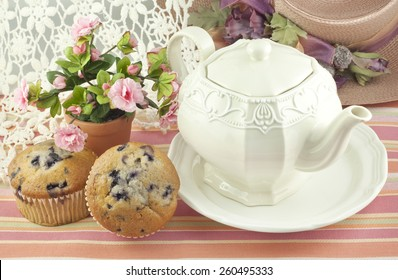 A ladies tea party with a vintage teapot, fresh baked blueberry muffins and pretty decorations, perfect for mothers day