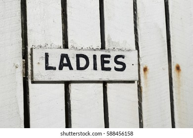 Ladies - vintage toilet sign on white painted wooden house