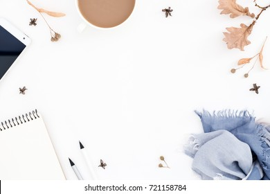 Ladies` workplace, women's things, smart phone, notebook, scarf, cup of coffee on white table. Round autumn composition