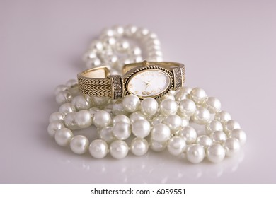 Ladies wristwatch sits atop a pearl necklace on white.