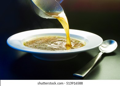Ladle broth to the pan with the broth background top view