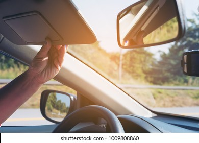 Lady adjust sun visor while driving car on highway road - interior car using concept