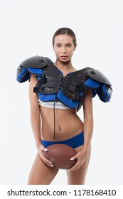 Lady in American football uniform with rugby ball