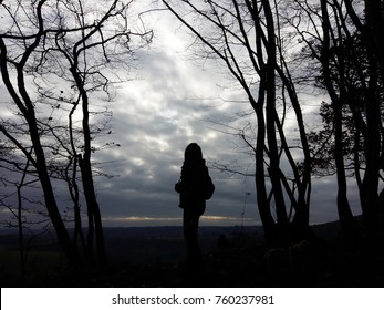 Lady asian silhouette standing alone on the mountain, looking dark sky and clouds, in the forest autumn season, look like very sadness, solitary, desolate, fear and lonely at Belgium country.