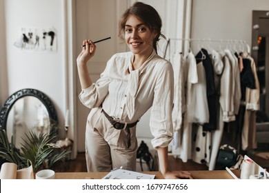 Lady in beige outfit poses at working place. Brunette woman in white shirt and linen pants smiles and holds pencil in office