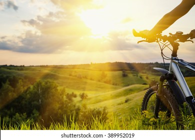 Lady with bicycle on a rural road with grass enjoying sunset