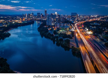 Lady Bird Lake in Austin, Texas featuring he downtown skyline and I-35 during sunset.