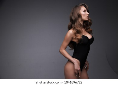 lady in black bodysuit. Beautiful wavy hair. fashion model isolated on grey