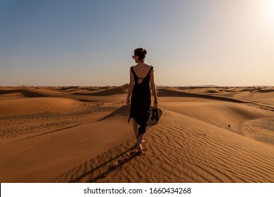 Lady in a black dress walks down the desert dune Towards the sunset, bare feet holding the shoes in her hands