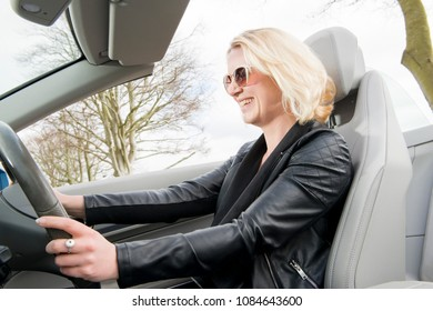 Lady in a black leather jacket and sunglasses, smiling and driving a convertible