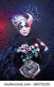 Lady in black. Young woman in creative image and with dry roses.