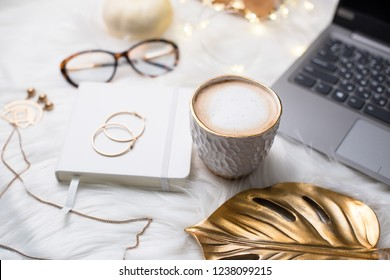 Lady bloggers white work space with gold details, laptop and cof