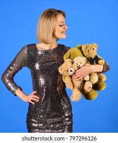 Lady with blond hair hugs cute toy bears. Woman holds heap of teddy bears on blue background. Tenderness and beauty concept. Girl with smiling curious face plays with beige soft toys.