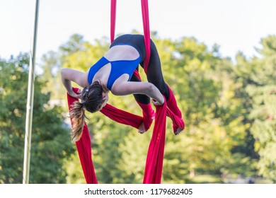 A lady in blue and black fitness outfit is hanging on a red ribbon is attempting to tied red ribbon on her legs